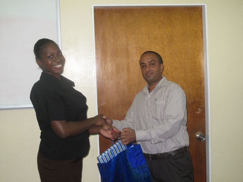 General-Manager-Christopher-Husbands-receives-token-from-Trainee-Marissa-Ottley